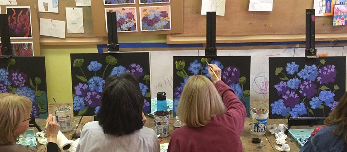 four artists painting purple flowers